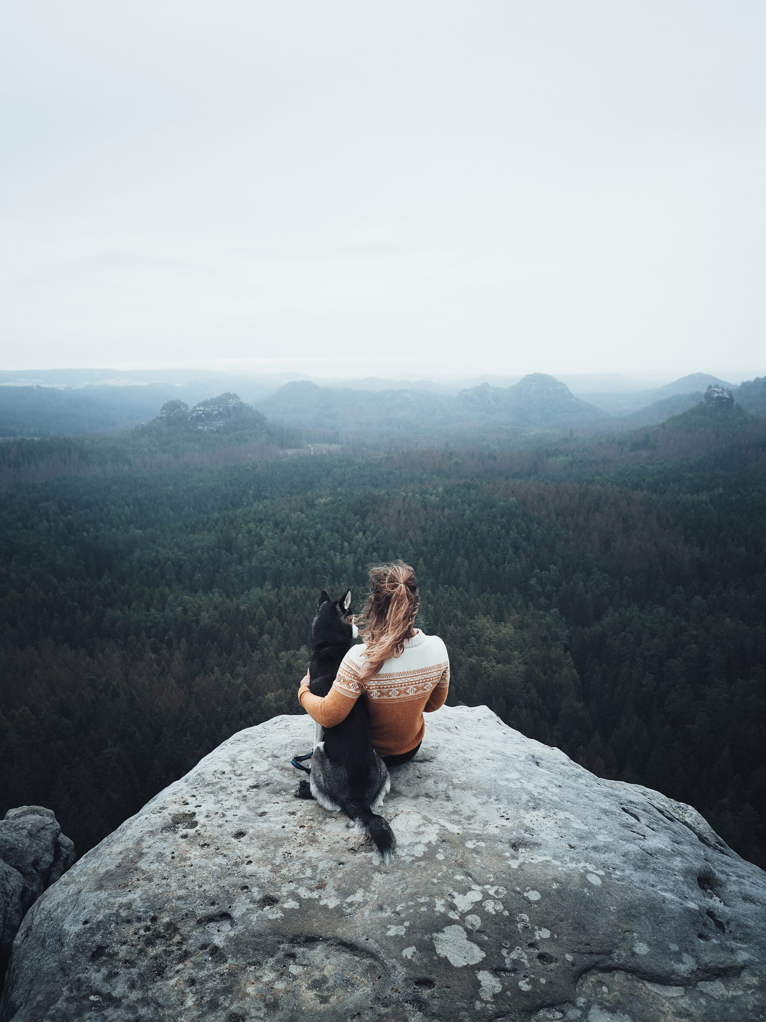 Frau mit Hund auf Fels