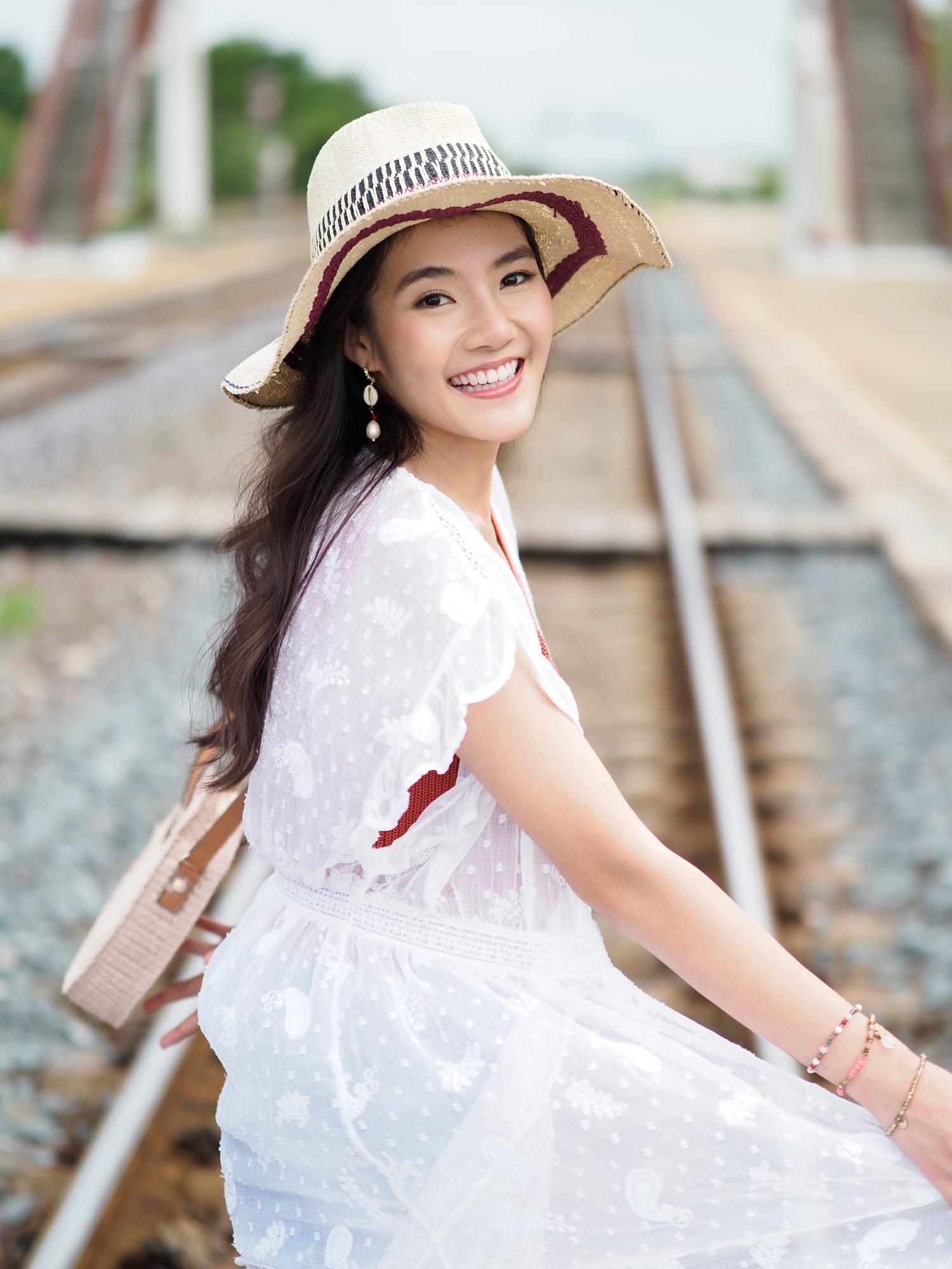 Frau mit Hut auf Bahngleisen