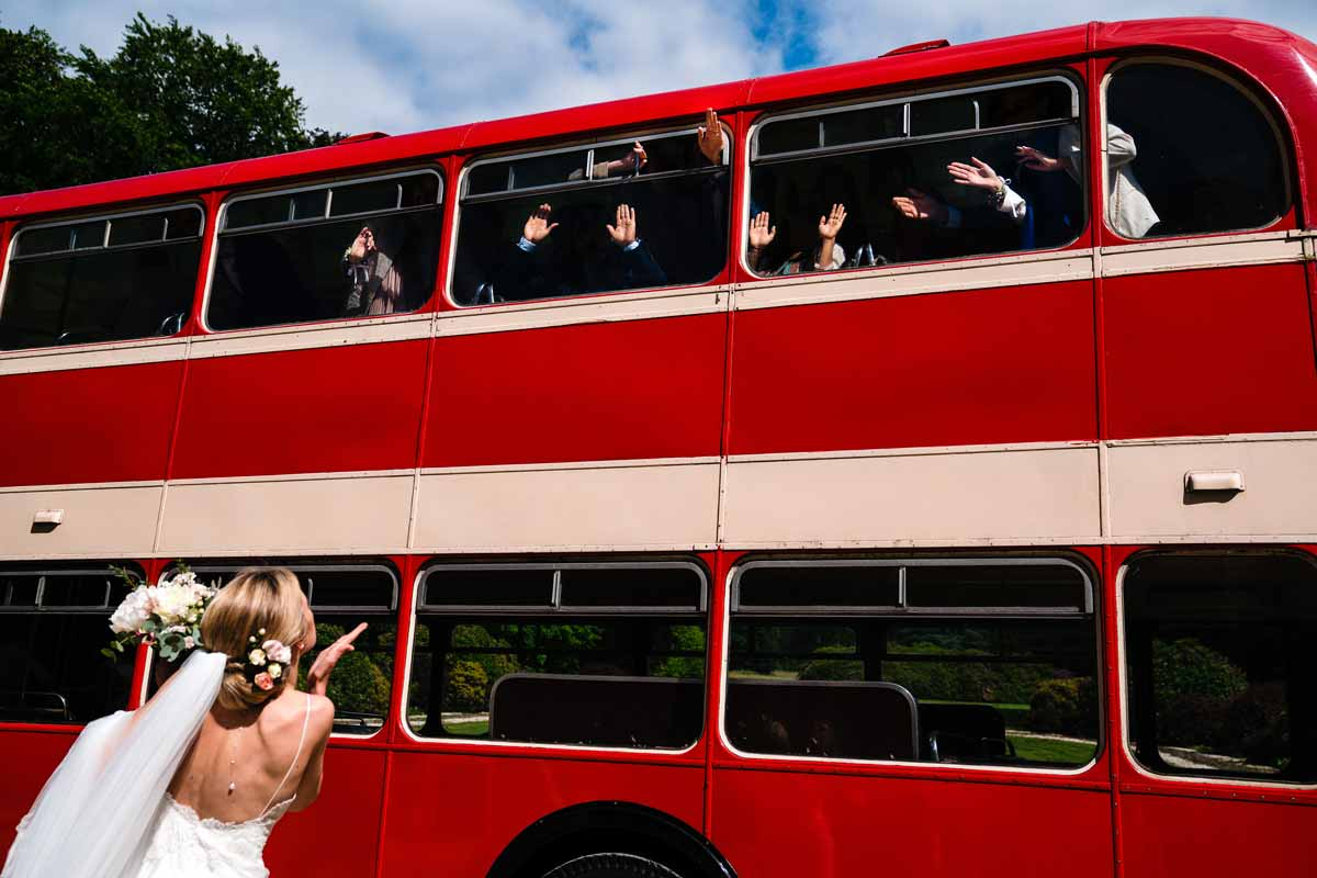 yves-schepers-sony-alpha-9-a-bride-blowing-her-groomsmen-a-kiss-as-they-sit-on-a-red-bus